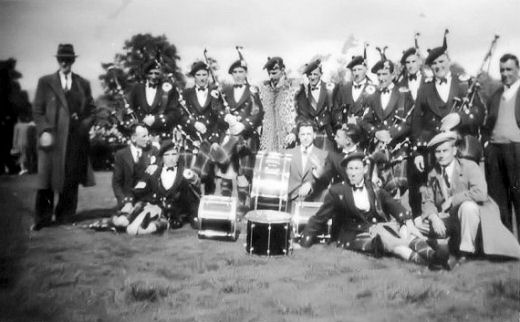 Bandsmen sitting on the grass, perhaps in the Christie Park